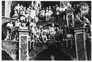 Giovani e bambini posano sulle arcate fuori la casa di Selvino